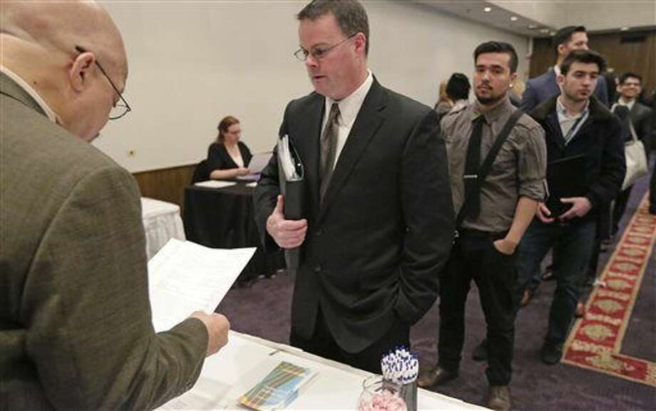 In this April 22, 2015 photo, Ralph Logan, general manager of Microtrain, left, speaks with James Smith who is seeking employment during a National Career Fairs job fair in Chicago. For months, U.S. employers have steadily added jobs even as global growth has flagged and financial markets have sunk. The jobs report for December on Friday, Jan. 8, 2016, may provide some hints of whether that trend can endure. (AP Photo/M. Spencer Green) Photo: M. Spencer Green