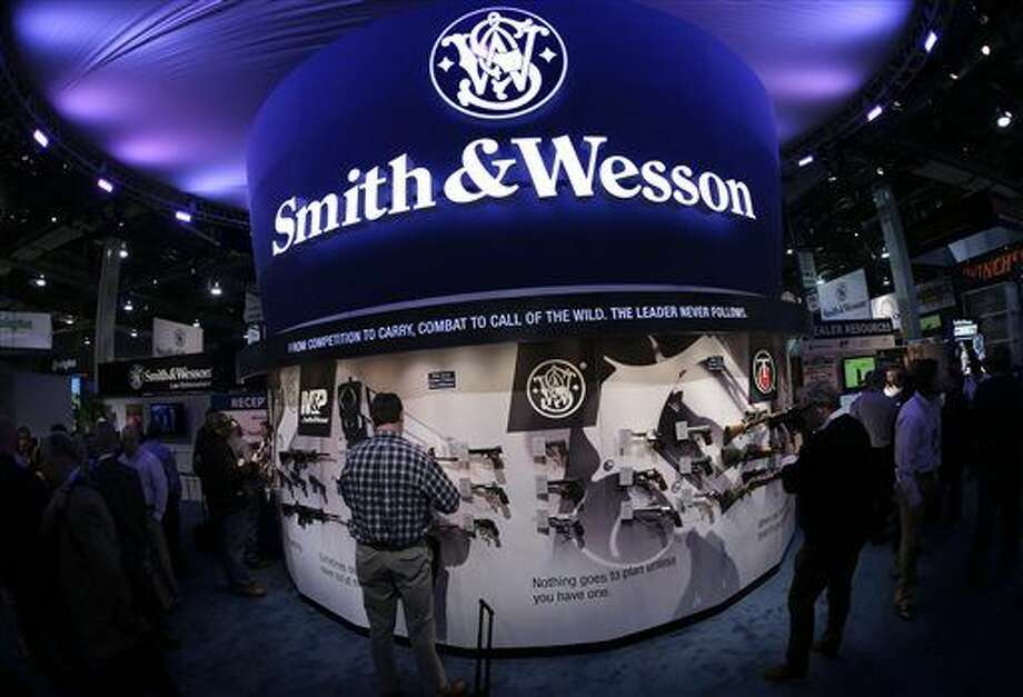 FILE - In this Tuesday, Jan. 14, 2014, file photo, trade show attendees examine handguns and rifles in the Smith & Wesson display boot at the Shooting Hunting and Outdoor Tradeshow, in Las Vegas. With all major markets in a severe sell-off Monday, Jan. 4, 2016, shares of companies that make guns surged as new data pointed to strong sales at the close of 2015, a year marked by mass shootings in Paris and California, and new political pressure to tighten regulations. Shares of Smith & Wesson Holding Corp. rose almost 6 percent Monday, one of the biggest percentage gains over the past year for the gunmaker. Its shares hit an all-time high two weeks earlier. (AP Photo/Julie Jacobson, File) Photo: Julie Jacobson