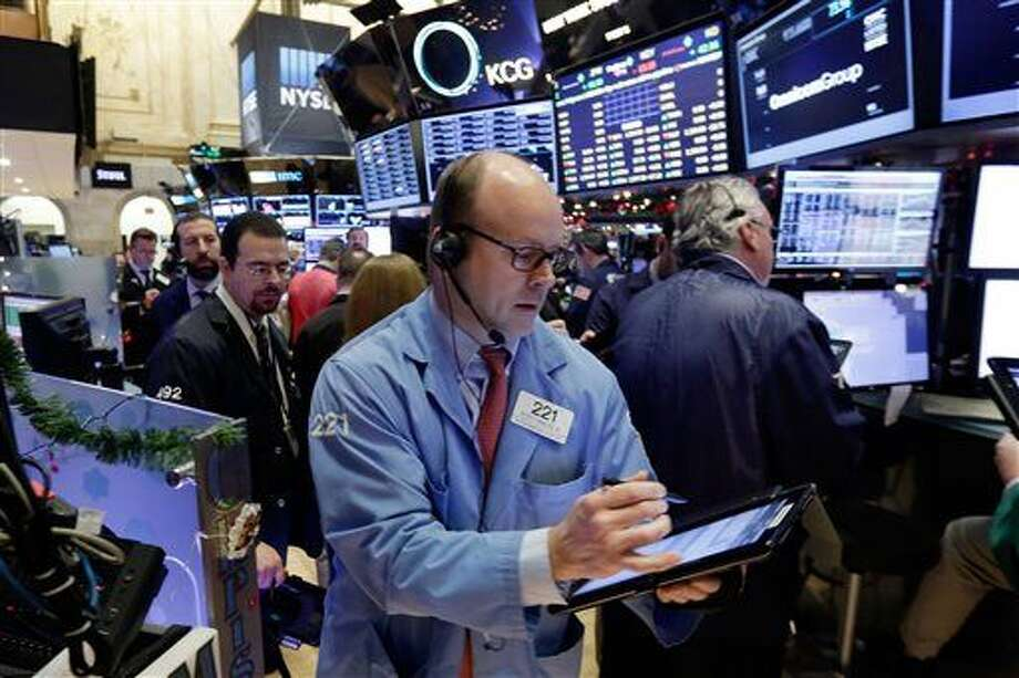Trader Peter Mancuso, center, works on the floor of the New York Stock Exchange, Monday, Jan. 4, 2016. U.S. stocks are opening 2016 on a grim note, dropping sharply after a plunge in China and declines in Europe. (AP Photo/Richard Drew) Photo: Richard Drew