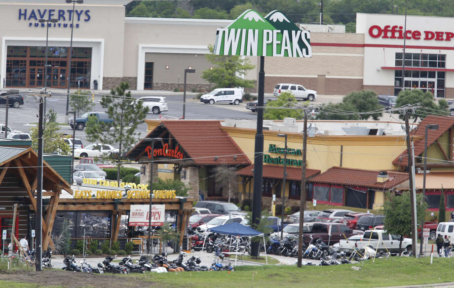 "Law enforcement officers investigate the parking lot of a Twin Peaks restaurant Sunday, May 17, 2015, in Waco, Texas. Waco Police Sgt. W. Patrick Swanton told KWTX-TV there were ""multiple victims"" after gunfire erupted between rival biker gangs at the restaurant. (Rod Aydelotte/Waco Tribune-Herald via AP) Photo: Rod Aydelotte"