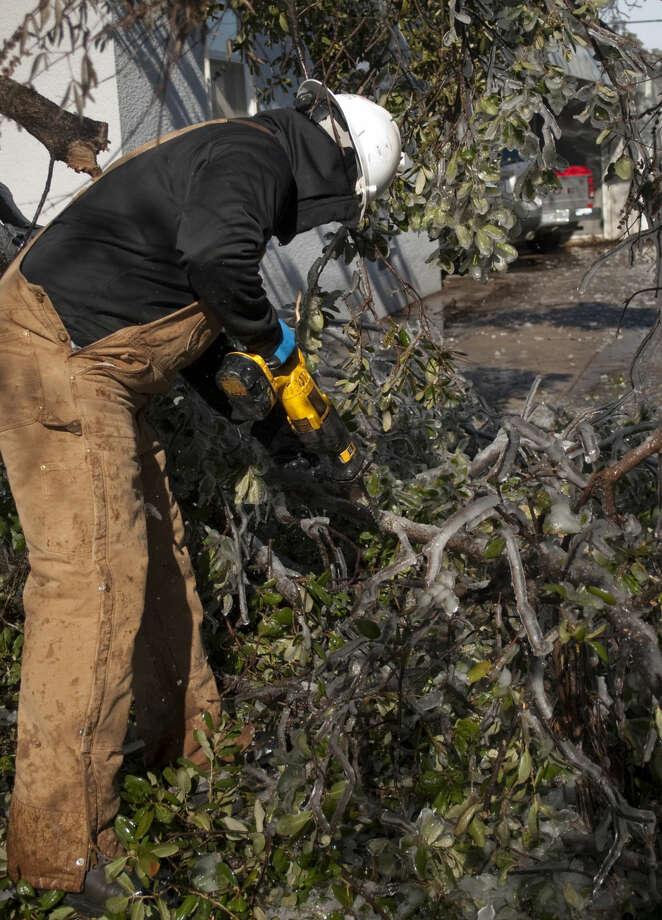 Che DeLaO helps clear downed branches from a neighbors driveway on W. Missouri Saturday, 01-03-15, after freezing temperatures and falling rain coated the city. Tim Fischer\Reporter-Telegram Photo: Tim Fischer