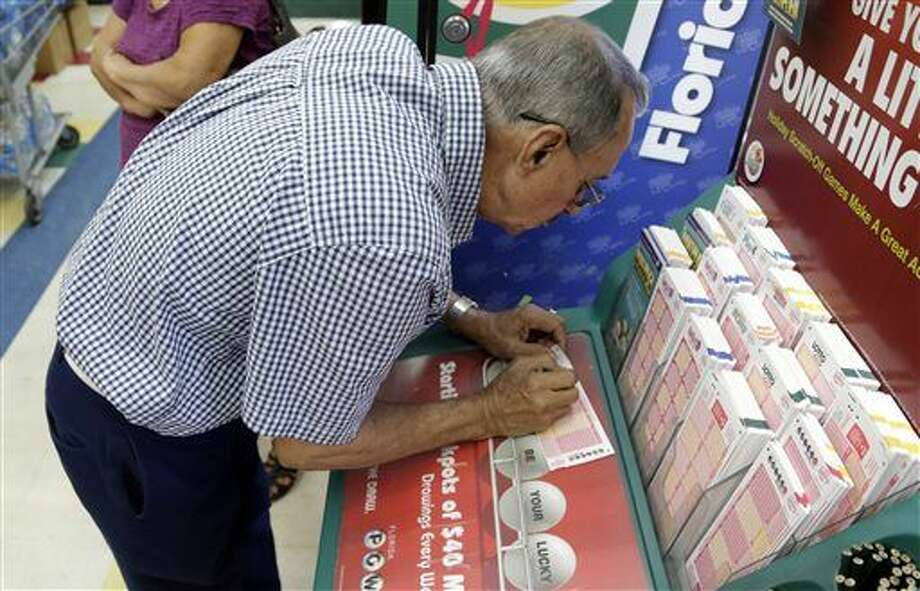 Julian Perez fills out a Powerball ticket, Saturday, Jan. 9, 2016, in Miami. Officials say it's increasingly likely that someone will win the $900 million Powerball jackpot, which grew by $100 million just hours before Saturday night's drawing. (AP Photo/Lynne Sladky) Photo: Lynne Sladky