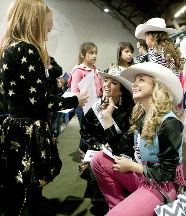 Miss Rodeo Sandhills Avery Greene and Miss Rodeo Sandhills Teen Kennady Johnson sign autographs during the Sandhills Rodeo on Friday at Ector County Coliseum. James Durbin/Reporter-Telegram Photo: JAMES DURBIN