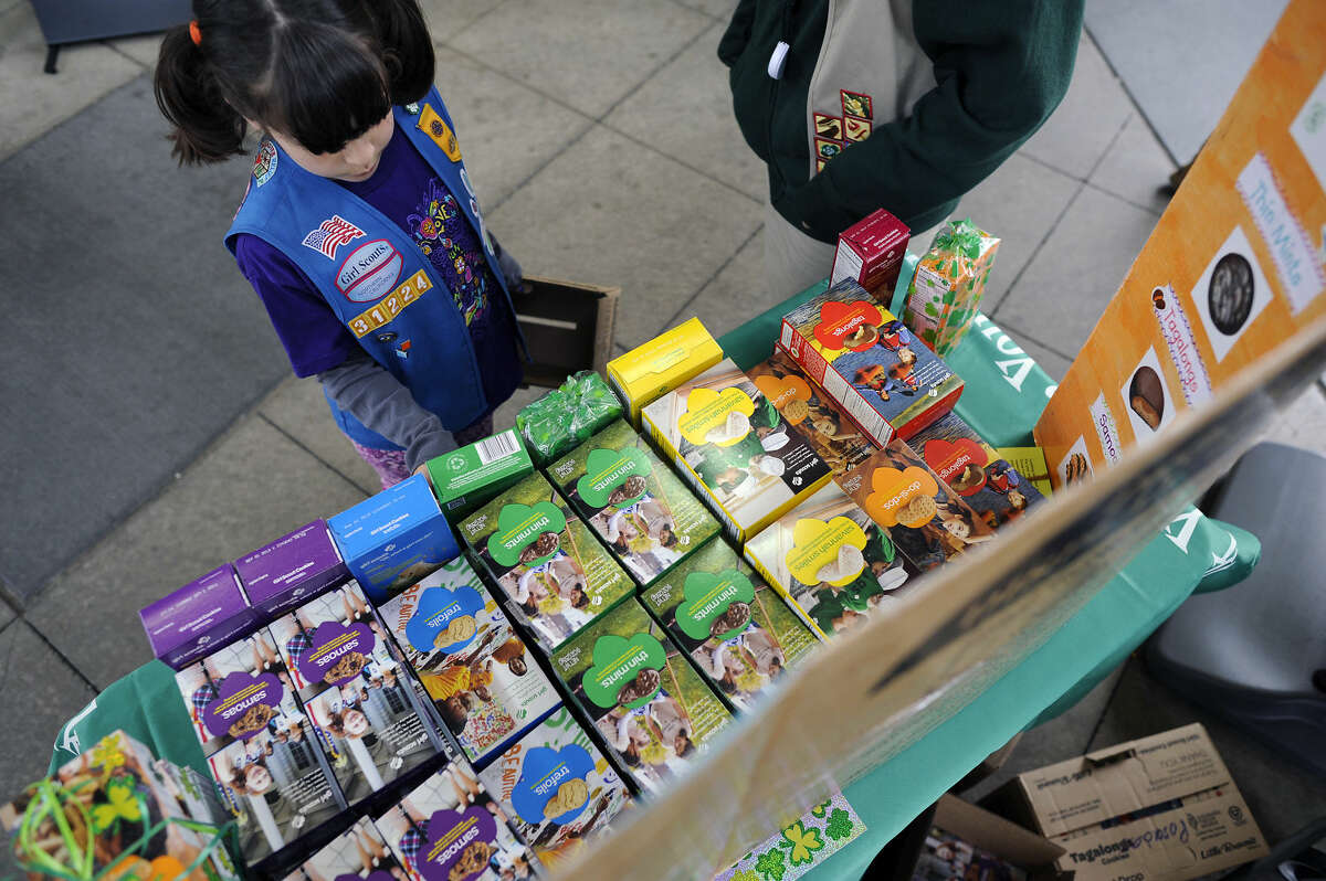 Girl Scout Kelly Aissa,7, restocks the table display of cookies for sale Thursday March 14th, 2013.