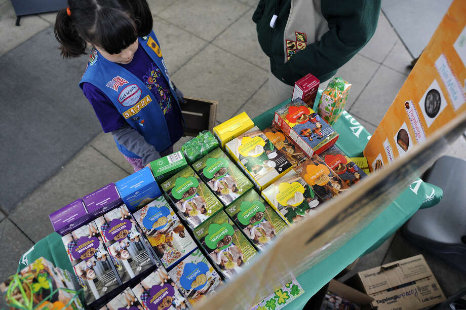 Girl Scout Kelly Aissa,7, restocks the table display of cookies for sale Thursday March 14th, 2013. Photo: Michael Short