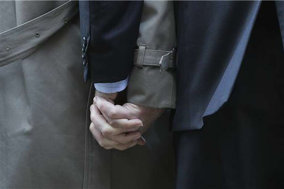 FILE - In this Feb. 12, 2014 file photo, Mark Phariss, left, holds the hand of his same-sex partner Victor Holmes, right, as they talk to the media outside the U.S. Federal Courthouse in San Antonio. Two signature Texas laws signed by outgoing Republican Gov. Rick Perry are on potentially shaky ground Wednesday, Jan. 7, 2015, when the 5th Circuit Court of Appeals in New Orleans considers whether the state can continue banning same-sex marriage and impose rigid standards on abortion providers. (AP Photo/Eric Gay, File) Photo: Eric Gay