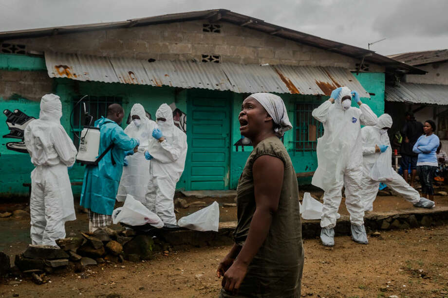 This Sept. 18, 2014, photograph by New York Times photographer Daniel Berehulak, part of a winning series, provided by Columbia University shows a relative grieving as a Liberian Red Cross burial team dresses in protective clothing before removing the body of a suspected Ebola victim in central Monrovia, Liberia. Berehulak is the winner of the 2015 Pulitzer Prize for Feature Photography, announced Monday, April 20, 2015, at Columbia University in New York. (Daniel Berehulak, New York Times, Columbia University via AP) Photo: Daniel Berehulak