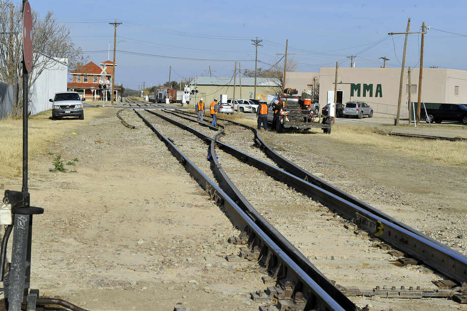 Rail workers continue improvements to the railway traversing through downtown San Angelo, Wednesday, Dec. 3, 2014 in San Angelo . The railroad tracks go through land owned by Lee Pfluger, developer and entrepenuer. Pfluger proposes to develop a hydraulic fracturing sand facility on the property raising concerns among the nearby property owners. The proposed facility includes silica sand brought in by rail and trucked out for the purpose of fracturing and oil production in the permian basin . (Kimberley Meyer/Chronicle) Photo: Kimberley Meyer