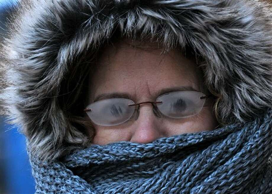 With temperatures below zero, Brenda Williams, 53, of Charleston, braves the cold to get her haircut downtown Charleston, W.Va.. Her glasses had frosted over and she could barely see. (AP Photo/The Daily Mail, Craig Cunningham) Photo: Craig Cunningham    / The Daily Mail