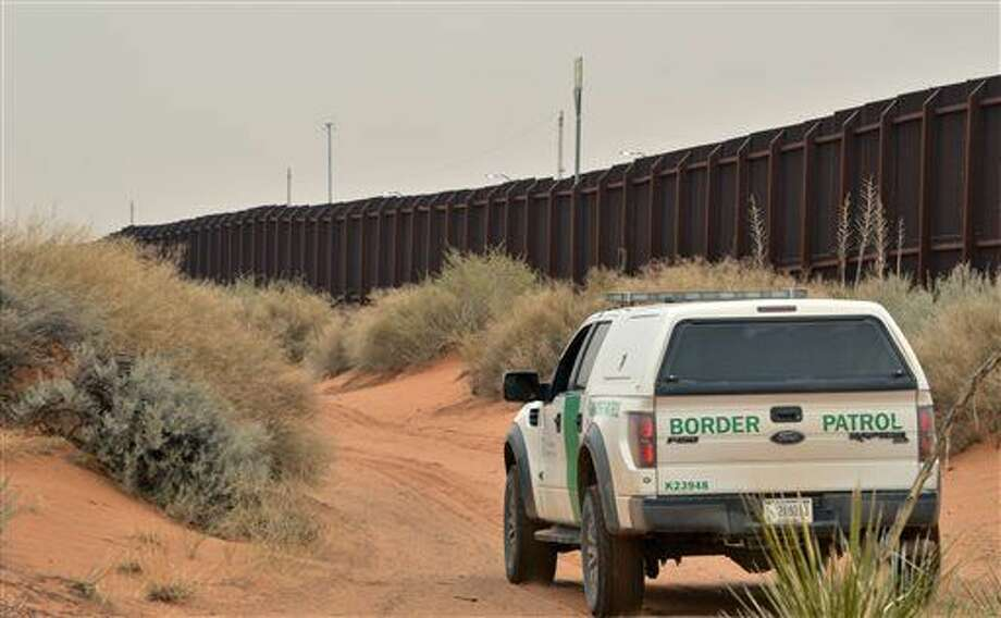 In this Jan. 4, 2016 photo, a U.S. Border Patrol agent drives near the U.S.-Mexico border fence in Santa Teresa, N.M. A spike in families and children arriving at the U.S. southern border from Central America has prompted fears of another crisis like the one that dominated national news during the summer of 2014. (AP Photo/Russell Contreras) Photo: Russell Contreras