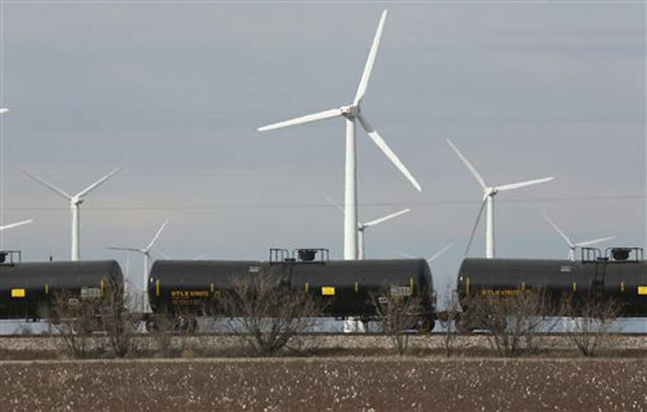 In this photo made Monday, Dec. 22, 2014, oil tankers train cars ride past windmills neat Sweetwater, Texas. Sweetwater is bracing for layoffs and budget cuts, anxious as oil prices fall and its largest investors pull back. (AP Photo/LM Otero) Photo: LM Otero