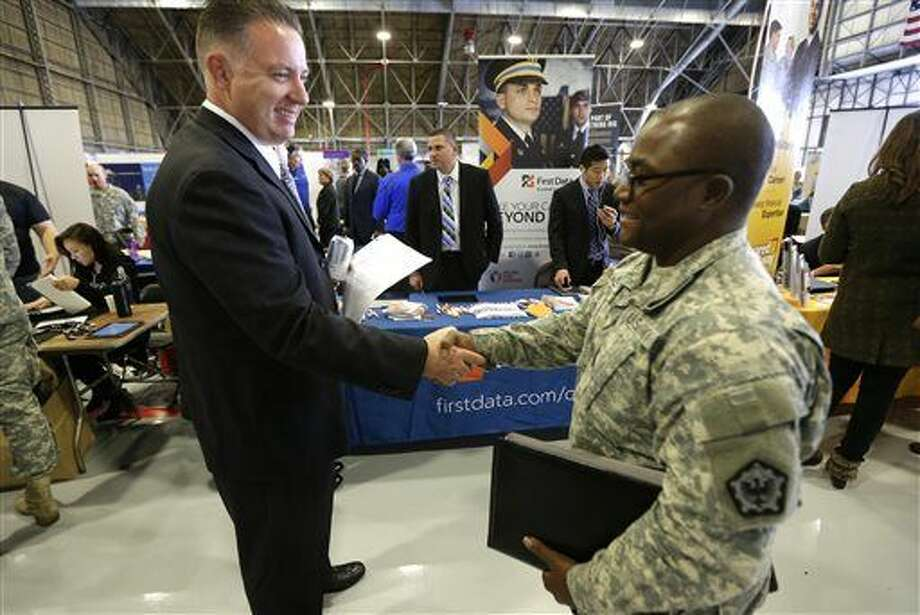 "FILE - In this Oct. 23, 2014 file photo, Joe Wilhelm, left, a recruiter with payment processing company First Data Corp., shakes hands with U.S. Army Spc. Vincent Knowles, at a job fair that was part of a ""transition summit"" intended to provide employment and educational information to soldiers who may exit military service in the next year, at Joint Base Lewis-McChord, Wash. The Labor Department releases employment data for December 2014 on Friday, Jan. 9, 2015. (AP Photo/Ted S. Warren, File) Photo: Ted S. Warren"