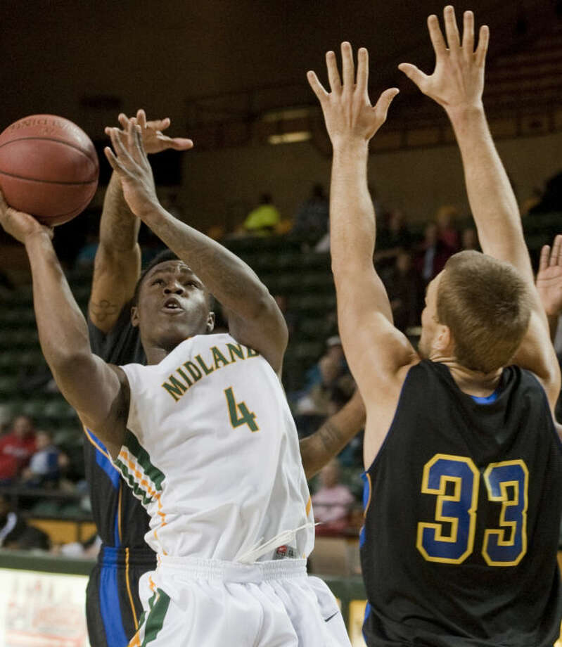 Midland College's Domonique Bul is fouled from behind by Frank Phillips' Stan Whittaker as Rokos Paulauskas defends Monday at Chaparral Center. Tim Fischer\Reporter-Telegram Photo: Tim Fischer