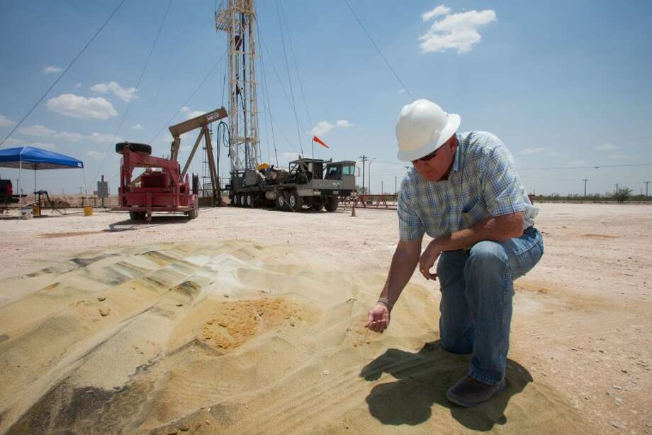 (FILE PHOTO) Tommy Taylor, drilling manager for Fasken Oil and Ranch, Ltd., inspects a pile of fracking sand deposited near an oil well where a pulling crew readies it for production. The Texas Tribune (Galbraith: Fracking Boom) Jerod Foster for The Texas Tribune. Photo: Jerod Foster
