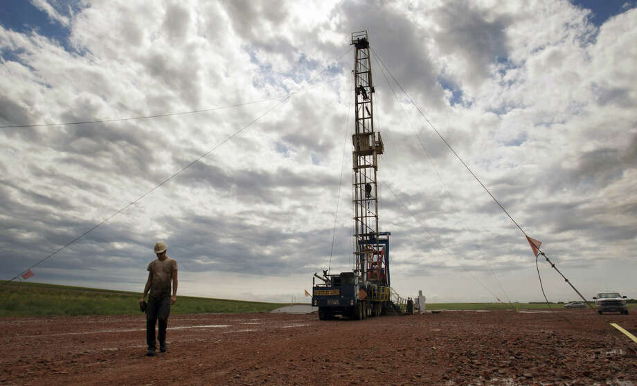 FILE - In this Tuesday, July 26, 2011 file photo, a worker walks by an oil derrick outside of Williston, N.D. Relief could be on the horizon for strapped public services in the Northern Plains' booming oil patch, as elected leaders in Montana and North Dakota move to steer more money into the region during the states' upcoming legislative sessions. (AP Photo/Gregory Bull, File) Photo: Gregory Bull