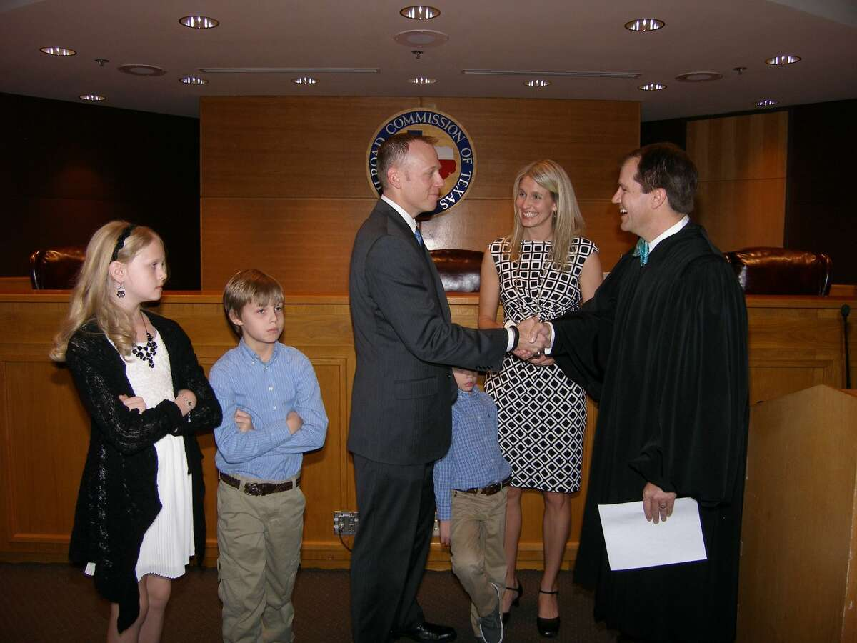 New Railroad Commissioner Ryan Switton is sworn in by Texas Supreme Court Justice Don Willett. His wife Jennifer and their three children accompany him.