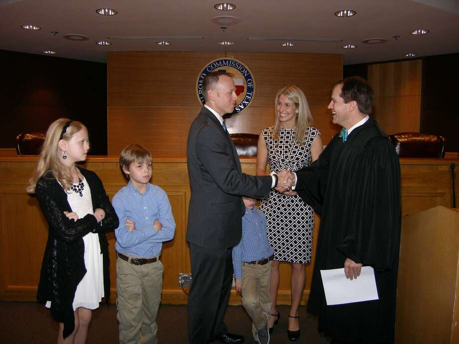 New Railroad Commissioner Ryan Switton is sworn in by Texas Supreme Court Justice Don Willett. His wife Jennifer and their three children accompany him. Photo: Photo Courtesy Railroad Commission