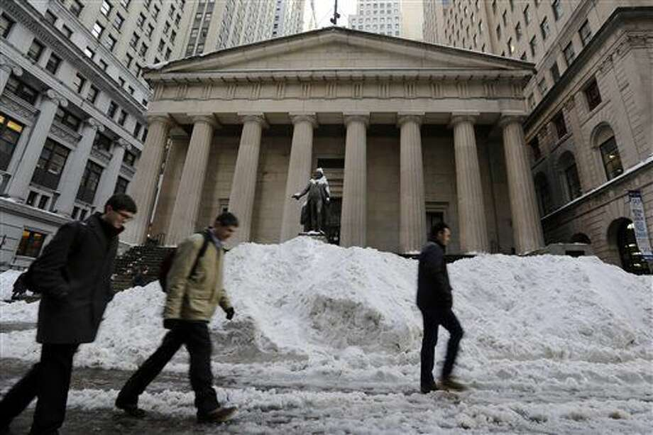 Morning commuters pass plowed snow on Wall Street in front of Federal Hall in New York's Financial District, Monday, Jan. 25, 2016. U.S. stocks are slipping Monday morning as energy prices retreat from a rally late last week. Mining and materials stocks are slumping as paper and packing companies lost ground. (AP Photo/Richard Drew) Photo: Richard Drew