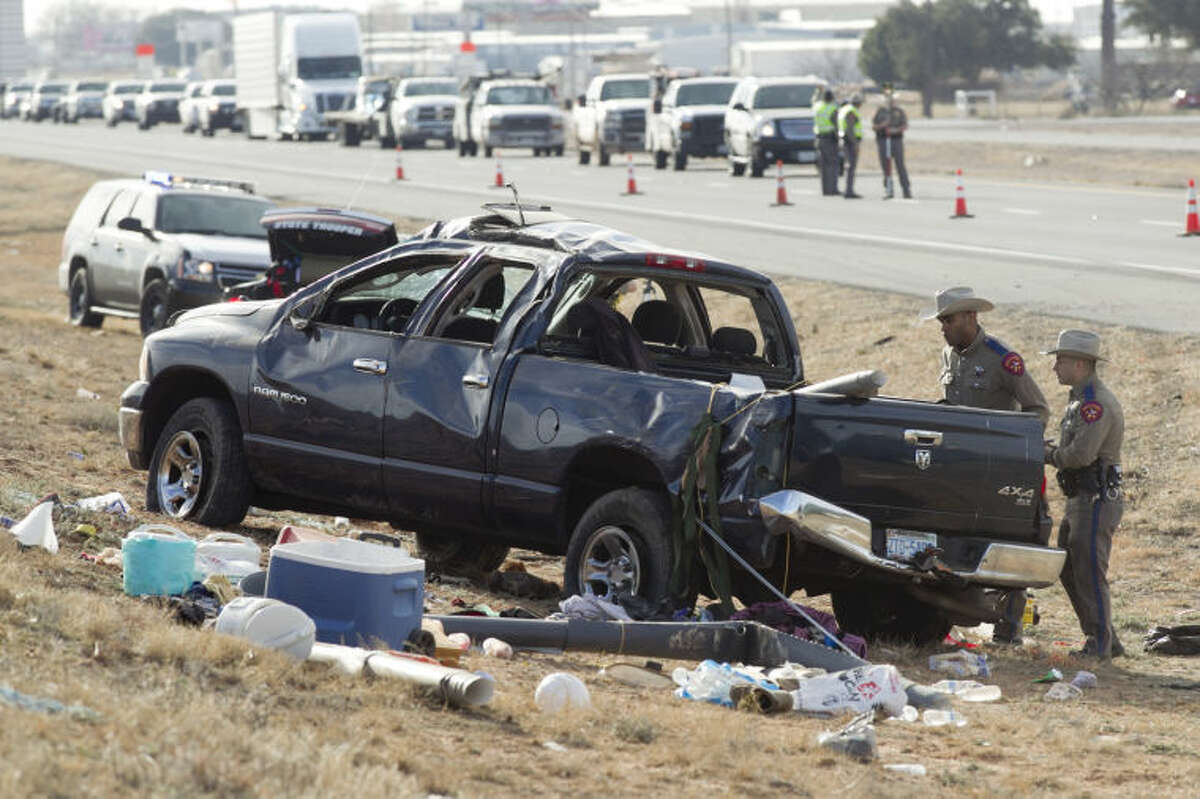 Public safety personnel investigate the scene of a fatal accident near the intersection of I-20 and F.M. 1788 on Thursday. A blue Dodge Ram was towing a green Honda Civic when the Ram lost control and rolled over, ejecting a passenger who was pronounced dead at the scene. James Durbin/Reporter-Telegram