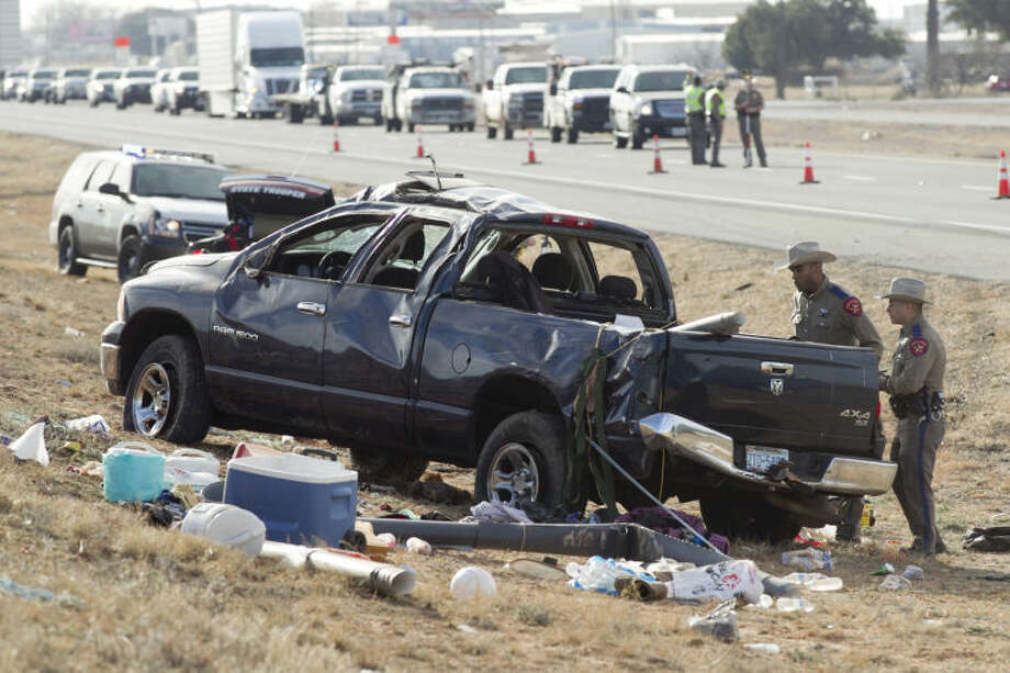 Public safety personnel investigate the scene of a fatal accident near the intersection of I-20 and F.M. 1788 on Thursday. A blue Dodge Ram was towing a green Honda Civic when the Ram lost control and rolled over, ejecting a passenger who was pronounced dead at the scene. James Durbin/Reporter-Telegram Photo: JAMES DURBIN