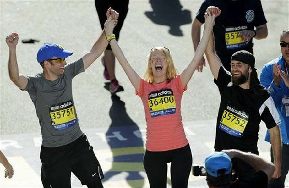 FILE - In this April 21, 2014 file photo, Timothy Haslet, left, and David Haslet, right, celebrate with their sister Adrianne Haslet-Davis at the finish line of the 118th Boston Marathon, after she completed a short distance of the course in Boston. Haslet-Davis said she is training to run the entire Boston Marathon on Monday, April 18, 2016. Haslet-Davis lost her left leg below the knee in the April 2013 bombing attacks, which killed three people and wounded more than 260 others. (AP Photo/Charles Krupa, File) Photo: Charles Krupa