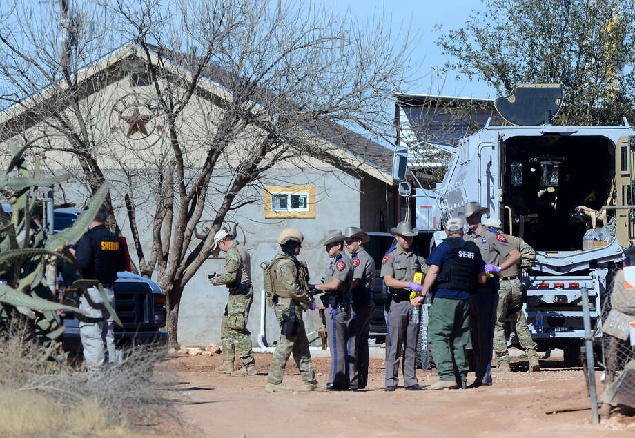 Midland law enforcement professionals work a scene near the 2700 block of South County Road 1195 where drugs, money, firearms, roosters and vehicles were seized in an apparent bust of a cock fighting ring, according to a statement from Midland County Sheriff Gary Painter, Saturday, Jan. 23, 2016. James Durbin/Reporter-Telegram Photo: James Durbin
