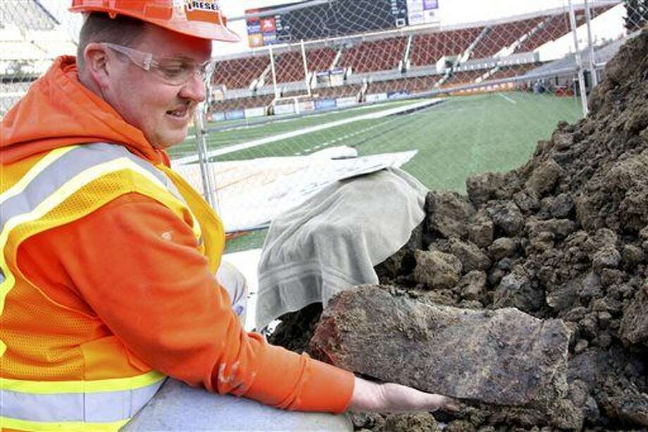 In this Jan. 26, 2016 photo provided by Oregon State University, Woodburn High School science teacher Dave Ellingson holds part of the pelvis of a mammoth found at an OSU construction site by a football field in Corvallis, Ore. Crews working on an expansion around Reser Stadium found a femur from one of the ancient elephants and bones from a bison and camel, all dating back 10,000 years. A spokesman says the OSU archaeologist believes the 10-foot pit where the remains were found could have been a pond or watering hole. (Theresa Hogue/Oregon State University via AP) Photo: Theresa Hogue