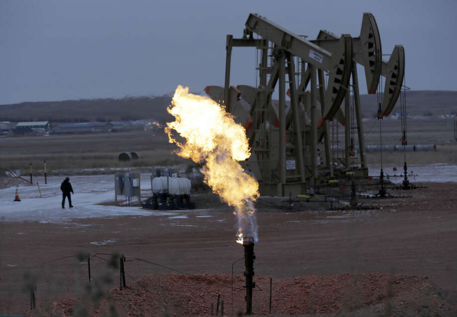In this Dec. 17, 2014 photo, workers tend to oil pump jacks behind a natural gas flare near Watford City, N.D. Natural gas, the nation's most prevalent heating fuel, is getting cheaper just as winter is arriving because of mild temperatures and plentiful supplies. (AP Photo/Eric Gay) Photo: Eric Gay