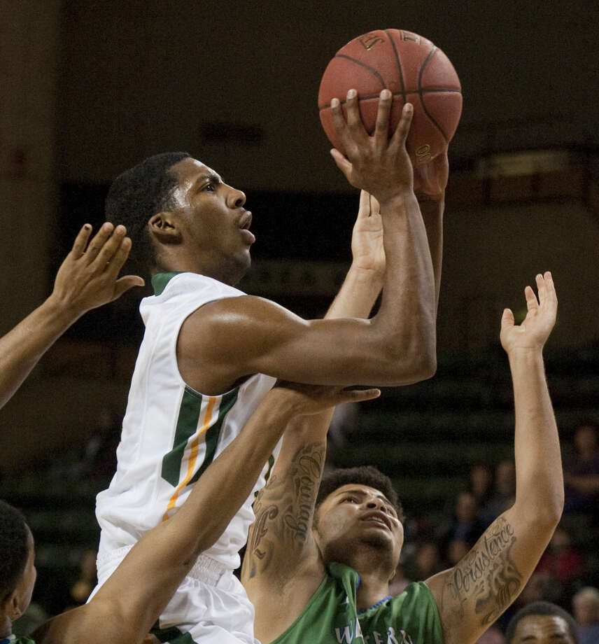 Midland College's Tyler Whitehead drives the lane between Western Texas' Jason Nunez, left and Shane Johnson Monday evening, 1-12-15, at the Chaparral Center. Tim Fischer\Reporter-Telegram Photo: Tim Fischer