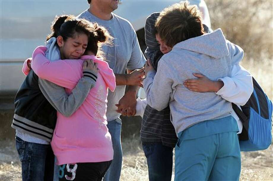 Students are reunited with family following a shooting at Berrendo Middle School, Tuesday, Jan. 14, 2014, in Roswell, N.M. Roswell police said the suspected shooter was arrested at the school, but authorities have not said if there were any injuries. The school has been placed on lockdown. No other details are yet available. (AP Photo/Roswell Daily Record, Mark Wilson) Photo: Mark Wilson / AP2014