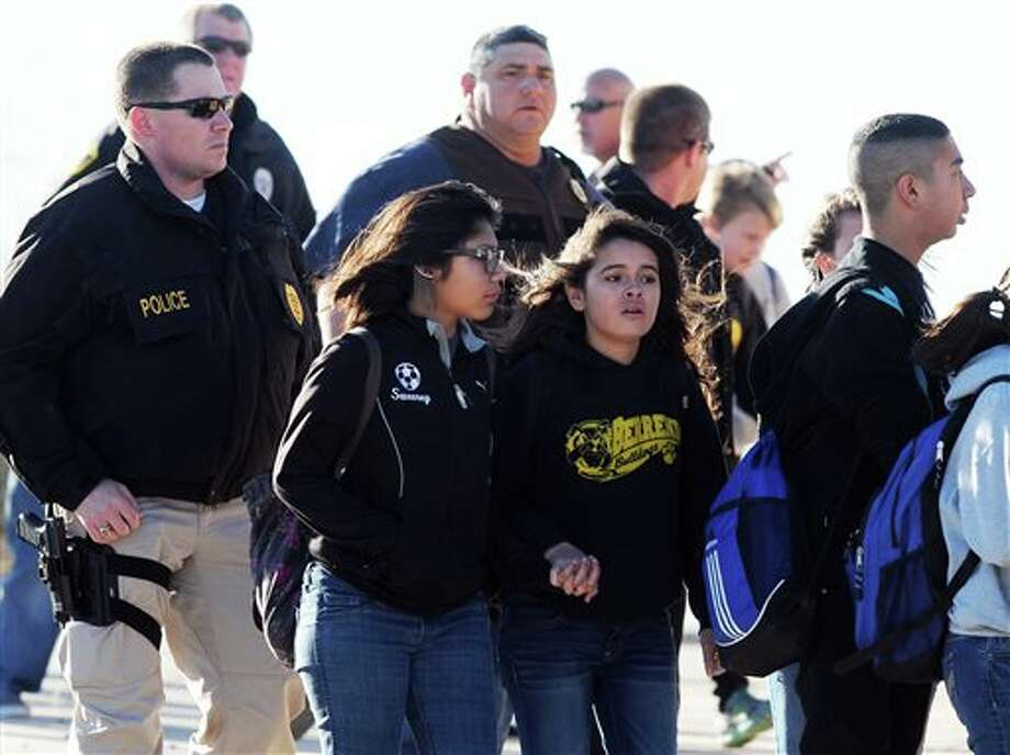 Students surrounded by officials are escorted from Berrendo Middle School after a shooting, Tuesday, Jan. 14, 2014, in Roswell, N.M. Roswell police said the suspected shooter was arrested at the school, but authorities have not said if there were any injuries. The school has been placed on lockdown. No other details are yet available. (AP Photo/Roswell Daily Record, Mark Wilson) Photo: Mark Wilson / Roswell Daily Record