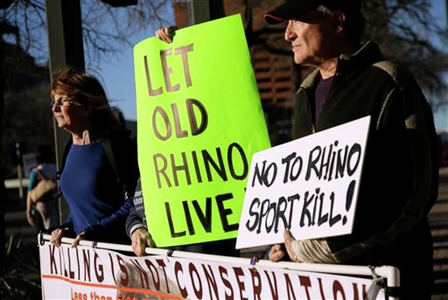 Pat Antonisse, left, of Dallas, Susan Oakey, center, of Dallas and Gary Angle, right, of Richardson, Texas, holds sign protesting outside the Dallas Convention Center where the Dallas Safari Club is holding its' weekend show and auction, Saturday, Jan. 11, 2014, in Dallas. Hunt the black rhino to save the black rhino. That's the Dallas Safari Club's approach to a fundraiser for efforts to protect the endangered species. The group hopes to raise more than $200,000 Saturday by auctioning off the right to shoot and kill a black rhinoceros in the African nation of Namibia. (AP Photo/Tony Gutierrez) Photo: Tony Gutierrez / AP