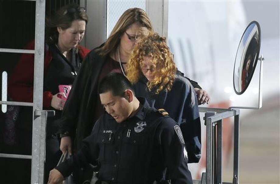 "Tonya Couch, center right, is escorted off a flight after her arrival to the Dallas/Fort Worth International Airport in Grapevine, Texas, Thursday, Jan. 7, 2016. Couch, mother of a fugitive teenager known for using an ""affluenza"" defense in a deadly drunken-driving case, waived extradition and was sent to Texas from California to face a charge of hindering the apprehension of a felon. (AP Photo/LM Otero) Photo: LM Otero"