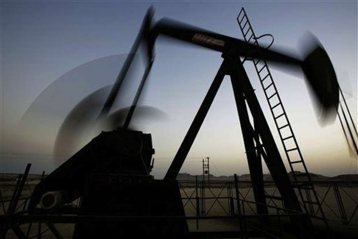 CORRECTS TRILLIONS TO BILLIONS - FILE - An oil pump works in the oil fields of Sakhir, Bahrain. Trends point to a new normal of minimal U.S. drilling activity.