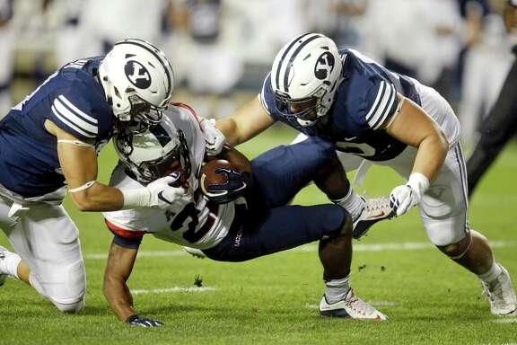 Connecticut running back Arkeel Newsome is tackled by BYU linebacker Sae Tautu (left) and defensive lineman Logan Taele (right) in the first half on Oct. 2, 2015, in Provo, Utah.