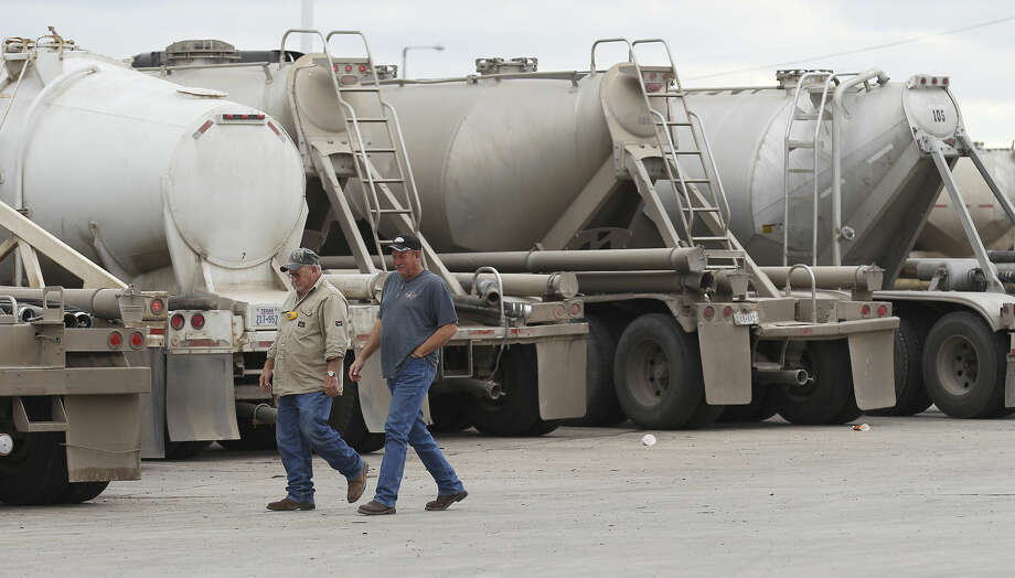 Two men walk past a row of tanker trucks at a gas station in Cotulla, Texas on Thursday, Dec. 11, 2014. The truck stop remained busy as oil production continues in the Eagle Ford region. (Kin Man Hui/San Antonio Express-News) Photo: Kin Man Hui