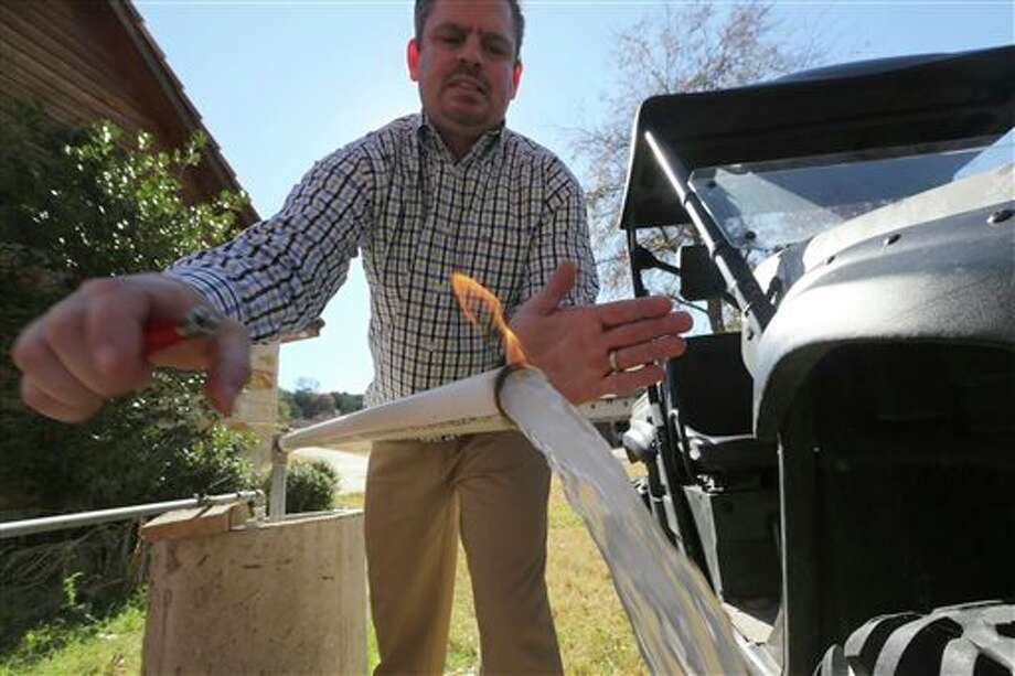 FILE - In this Nov. 26, 2012 file photo, Steve Lipsky demonstrates how his well water ignites when he puts a flame to the flowing well spigot outside his family's home in rural Parker County near Weatherford, Texas. A preliminary analysis of testing in the past year of North Texas water contaminated with explosive methane has found that the problem has spread to more residential wells, and scientists analyzing those samples believe the new evidence more conclusively points to a nearby gas drilling operation as the source of the problem. (AP Photo/LM Otero, file) Photo: LM Otero / AP