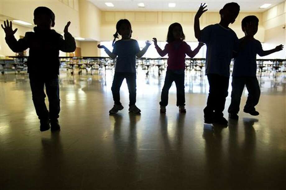 Elementary school children from School at St. George Place dance following the Nintendo Wii Just Dance video game as part of their physical education class, Friday, Jan. 10, 2014. The physical education teacher Brittany Stags made the request for the Nintendo Wii funds through DonorsChoose.org. (AP {Photo/ Houston Chronicle, Marie D. De Jesus) Photo: Marie D. De Jesus / Houston Chronicle