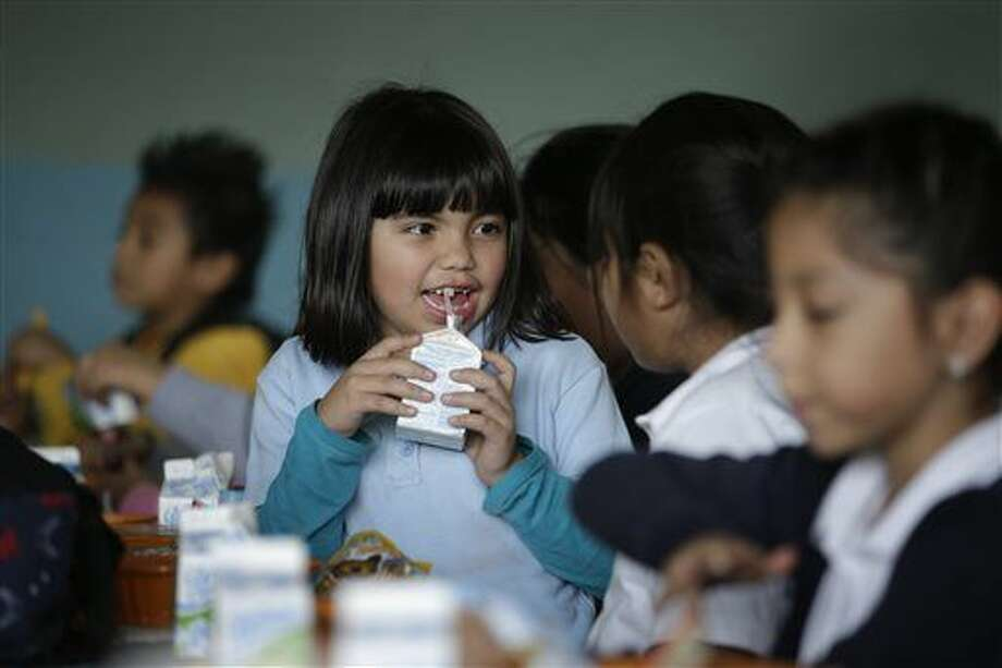 Hazel Loarca, 7, drinks her milk in the cafeteria area at Kingsley Elementary School, Tuesday, Jan. 13, 2015, in Los Angeles. Many of the students at the school in a low-income neighborhood of Los Angeles eat breakfast and lunch provided by the school. For the nearly 100 enrolled in the afterschool program, another meal is served: supper. The nation's second largest school district is doubling the number of students served dinner, with an eye toward eventually offering it at every school. (AP Photo/Jae C. Hong) Photo: Jae C. Hong