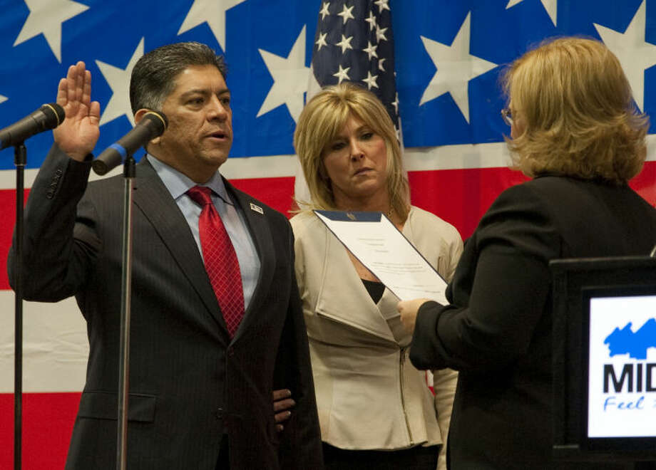 Jerry Morales, with his wife Meredith at his side, takes the oath of office for Mayor as city secretary, Amy Turner, performs the ceremony Monday at the Midland Center. Mayor Jerry Morales on Monday morning turned in his paperwork to run for a second term.  Tim Fischer\Reporter-Telegram