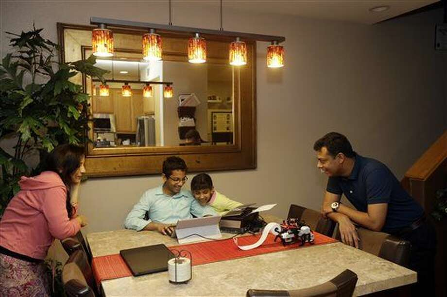 Shubham Banerjee, center left, works on a prototype for his braille printer joined by his family including mom Malini, left, sister Anoushka, 8, center right, and dad Neil, right, at home Tuesday, Jan. 6, 2015, in Santa Clara, Calif. Banerjee launched a company to develop a low-cost machine to print Braille materials for the blind. It's based on a prototype he built with his Lego robotics kit for a school science fair project. Last month, tech giant Intel Corp. invested in his startup, Braigo Labs, making the 8th grader the youngest entrepreneur to receive venture capital funding. (AP Photo/Marcio Jose Sanchez) Photo: Marcio Jose Sanchez