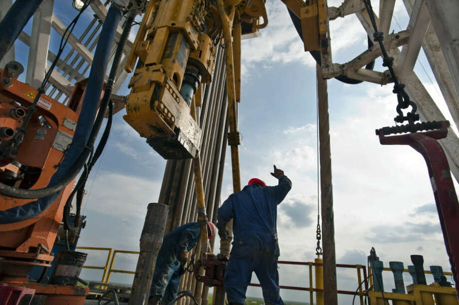 A floor hand signals to the driller to pull the pipe from the mouse hole on Orion Drilling Co.'s Perseus drilling rig near Encinal in Webb County, Texas, U.S., on Monday, March 26, 2012. The Perseus is drilling for oil and gas in the Eagle Ford Shale, a sedimentary rock formation underlying an area of South and East Texas. Photographer: Eddie Seal/Bloomberg