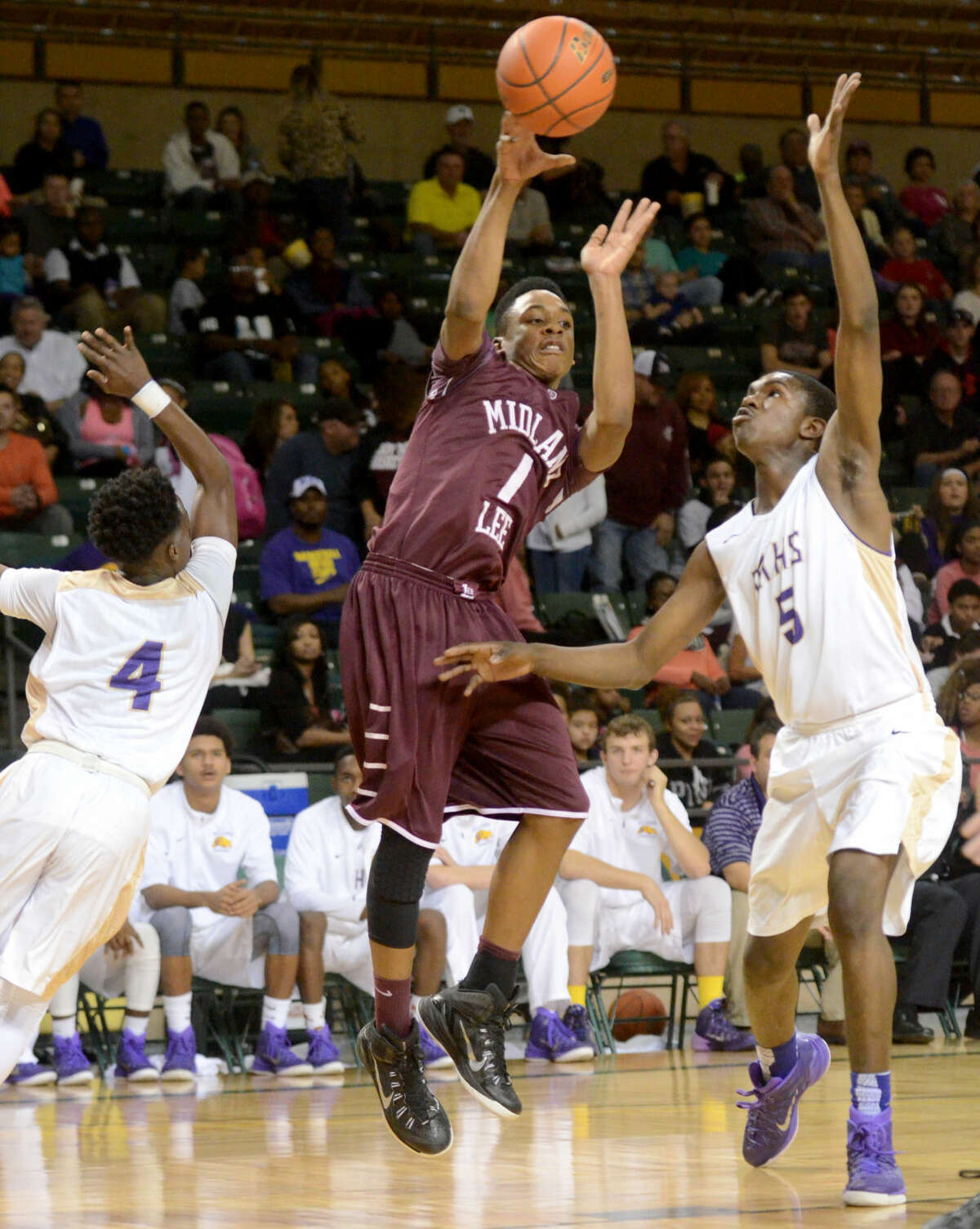 Midland High's A.D. Johnson (4) and Gary Ringo (5) try to block a shot from Lee High's Semaj Davis (1) on Tuesday, Jan. 20, 2015 at Chaparral Center. James Durbin/Reporter-Telegram