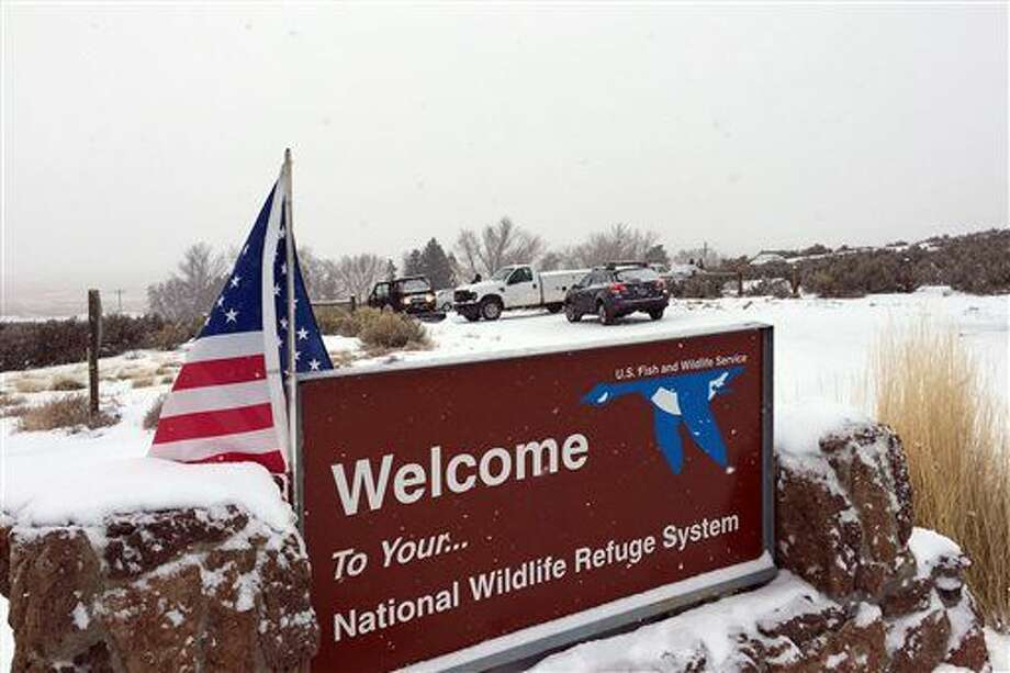 ADDS DETAILS OF SOME VEHICLES SEEN AT THE ENTRANCE - An sign of the National Wildlife Refuge System is seen at an entry of the wildlife refuge, where some vehicles are seen used to block access to the inside of the refuge, about 30 miles southeast of Burns, Ore., Sunday, Jan. 3, 2016. Armed protesters are occupying a building at the national wildlife refuge and asking militia members around the country to join them. The protesters went to Malheur National Wildlife Refuge on Saturday following a peaceful rally in support of two Oregon ranchers facing additional prison time for arson. (Les Zaitz/The Oregonian via AP) MANDATORY CREDIT Photo: Les Zaitz
