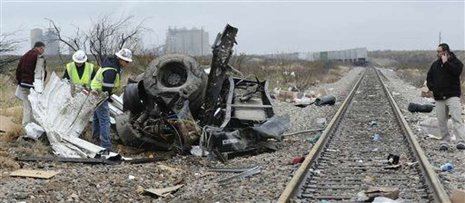 Authorities investigate the scene of a prison bus crash, Wednesday, Jan. 14, 2015, in Penwell, Texas. Law enforcement officials said the bus, carrying prisoners and corrections officers, fell from an overpass in West Texas and collided with a passing freight train, killing at least 10 people. (AP Photo/Odessa American, Mark Sterkel) Photo: Mark Sterkel