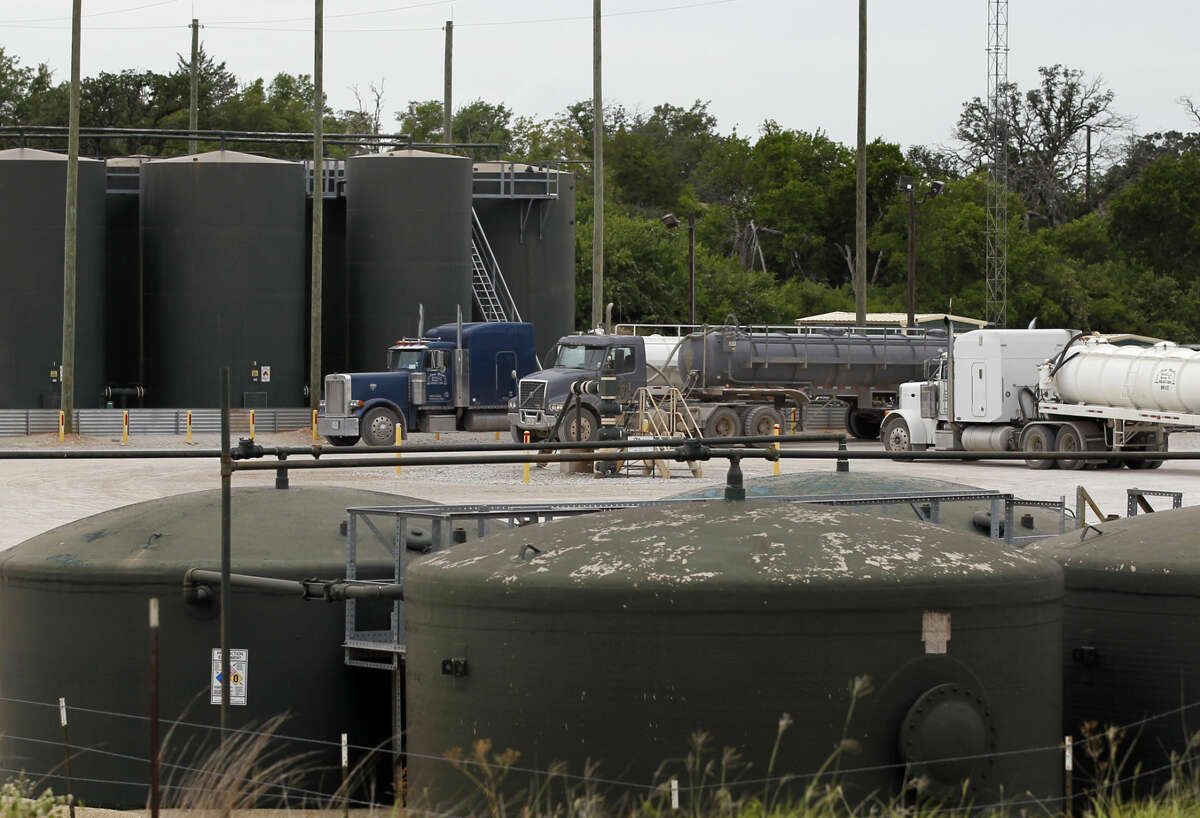 Tractor trailer trucks line up at an XTO Energy Inc. well site waiting to dump their fluid contents into a holding tank, Saturday, June 21, 2014, in Azle, Texas. Earthquakes used to be unheard of on the vast stretches of prairie that unroll across Texas and Oklahoma. But in recent years, temblors have become commonplace. (AP Photo/Tony Gutierrez)