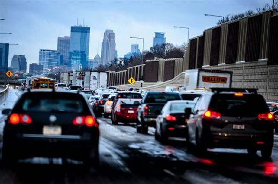 In this Monday, Nov. 10, 2014 photo, traffic crawls into downtown Minneapolis, Minn from the south along I-35W as an early snow was compressed into a slippery mess. Minnesota motorists can expect more company on the roads around Thanksgiving due to low gas prices and an improving economy. AAA is reporting that 41.3 million people will drive 50 miles or more from home during the upcoming holiday weekend that runs from Wednesday to Sunday. (AP Photo/The Star Tribune, Glen Stubbe) MANDATORY CREDIT; ST. PAUL PIONEER PRESS OUT; MAGS OUT; TWIN CITIES LOCAL TELEVISION OUT Photo: Glen Stubbe
