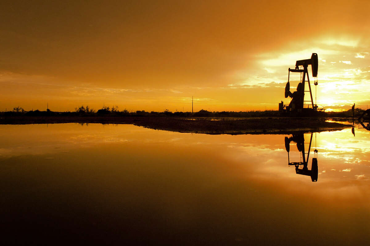Standing water reflects the sunset behind a pumpjack near the intersection of S County Rd 1130 and Interstate 20 on Wednesday. James Durbin/Reporter-Telegram