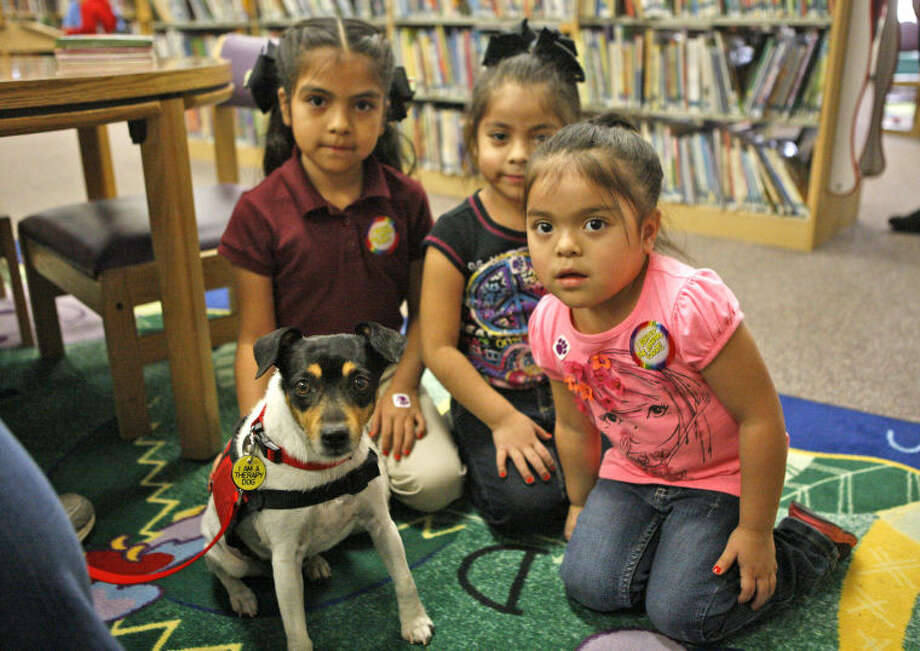 Therapy dogs assist children with reading difficulties on Tuesday at the Midland County Public Library downtown. James Durbin/Reporter-Telegram Photo: JAMES DURBIN