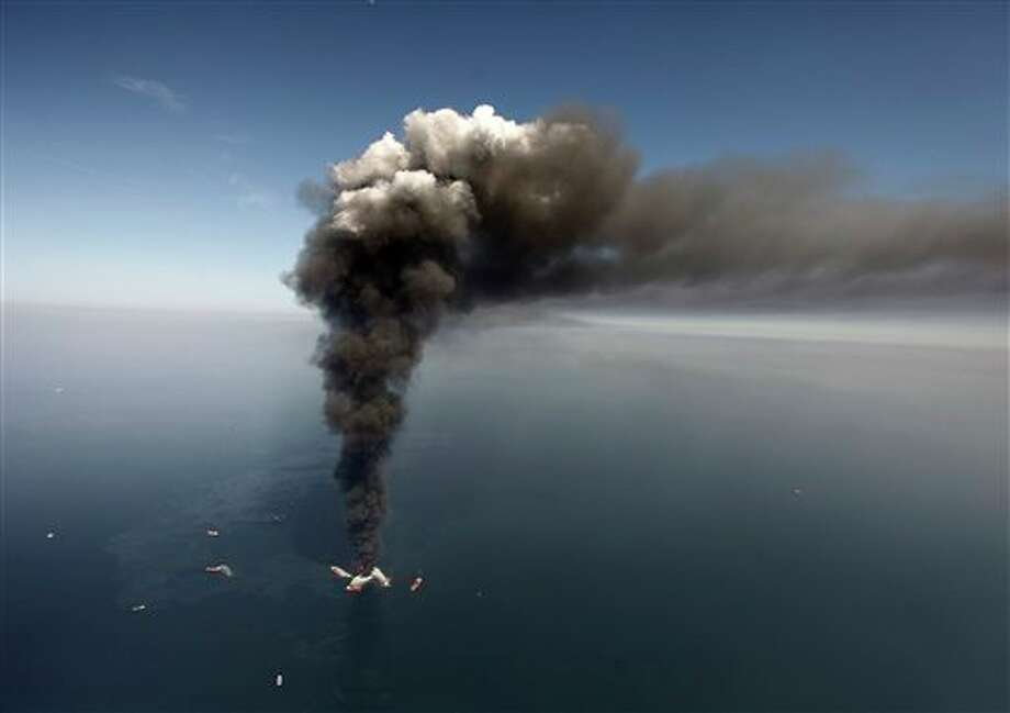 FILE - In this Wednesday, April 21, 2010 file photo, oil can be seen in the Gulf of Mexico, more than 50 miles southeast of Venice on Louisiana's tip, as a large plume of smoke rises from fires on BP's Deepwater Horizon offshore oil rig. An April 20, 2010 explosion at the offshore platform killed 11 men, and the subsequent leak released an estimated 172 million gallons of petroleum into the gulf. The Gulf oil spill settlement trial has started in New Orleans, Monday, Feb. 25, 2013. U.S. District Judge Carl Barbier is scheduled to hear several hours of opening statements Monday by lawyers for the companies, federal and state governments and others who sued over the disaster. Barbier is hearing the case without a jury. The trial is designed to identify the causes of BP's well blowout and assign percentages of fault to the companies. (AP Photo/Gerald Herbert, File) Photo: Gerald Herbert / AP